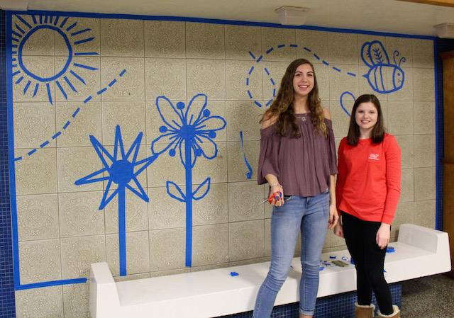 Jessica Eanes and Erin Wojkowski working on their tape art project.