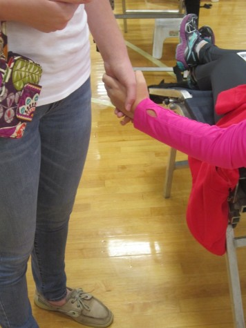 Volunteer Kayla Morgan holds the hand of a brave donating friend.