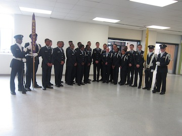 Drill Team posing for commemorative pictures   while proudly pointing to the MHS flag