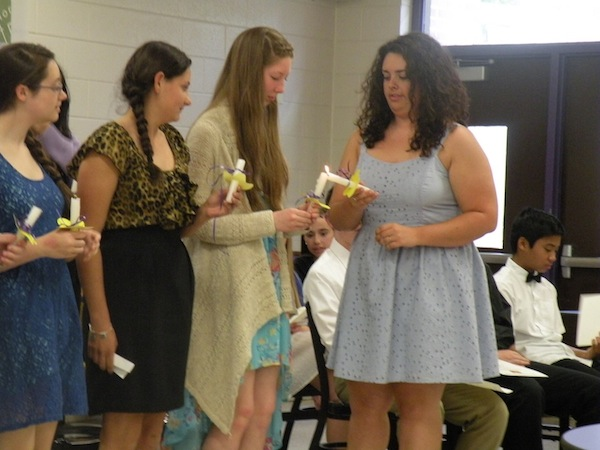 French Honor Society President Emily Moliken begins lighting candles using mother candle