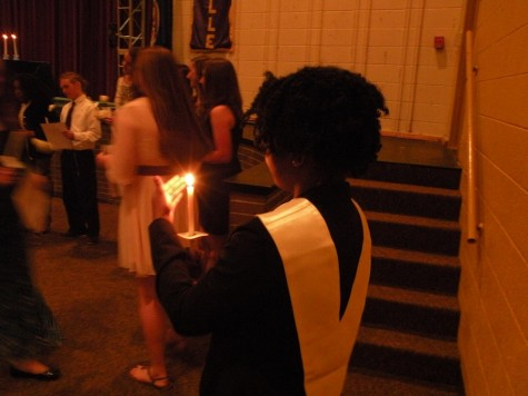 NHS historian Mbiye Kasonga carries the mother candle for the ceremony
