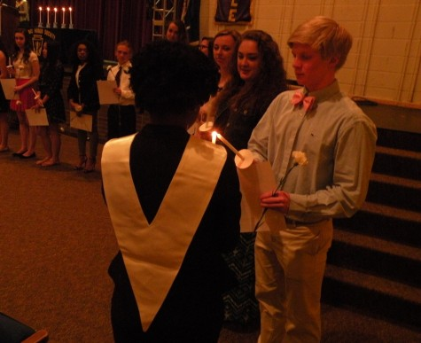 The inductees light their candles using the flame of the mother candle