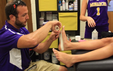 Athletic trainer Jonathan Hornsby bandages an injured athlete