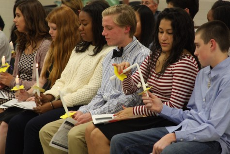 Spanish Honor Society inductees light their candles before saying the Spanish honor pledge.