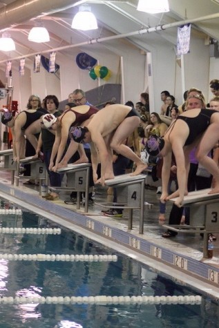 Menchville swimmers line up and get in starting position to kick off the swim meet.