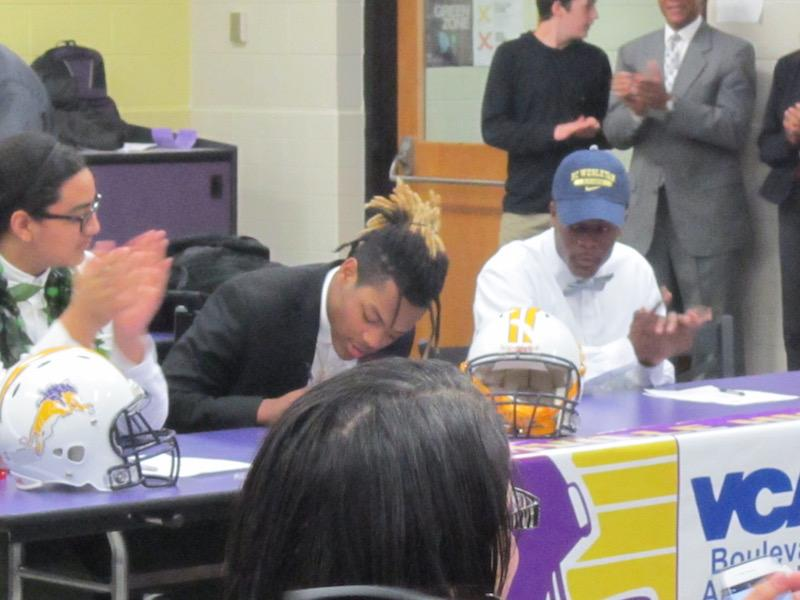 Ray Savage III signing his letter of intent to play football for the University of Virginia.