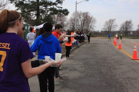 French and Spanish National Honor Society provide water to the runners passing by.