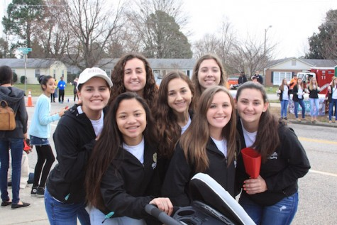 The Varsity Field Hockey team cheers on runners passing by to keep them motivated.