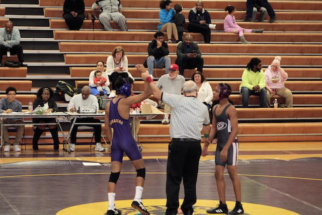 Tony Sales has hand raised after he wins his match.