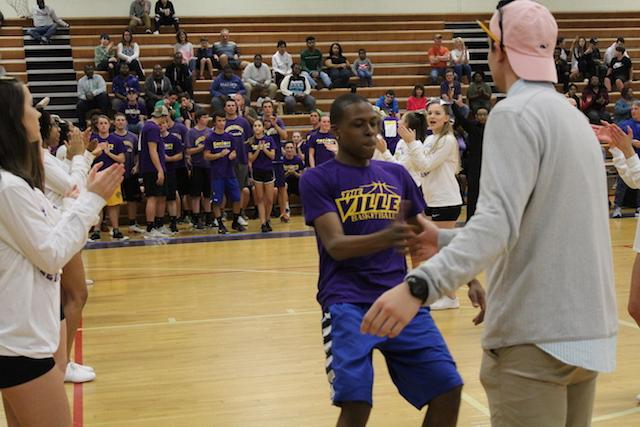 William Mclean-Burrell and Coach Thomas Carr doing their handshake for the starting lineup.