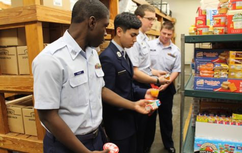 Javon Carter, Timothy Pasaoa, Patrick Mathias, and Zach Corbin passing down food to package back-packs.