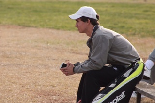 Brandon Mueller watches his teammates compete after winning his individual match.  He later won his doubles match with partner Hunter Dangerfield.