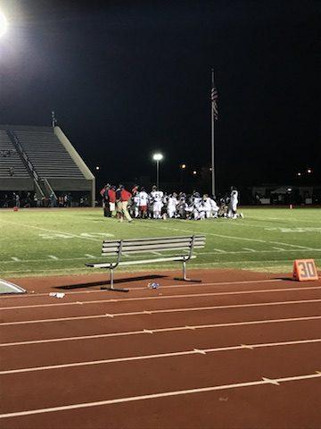 After the win, Menchvilles Varsity Football team huddles on the field.