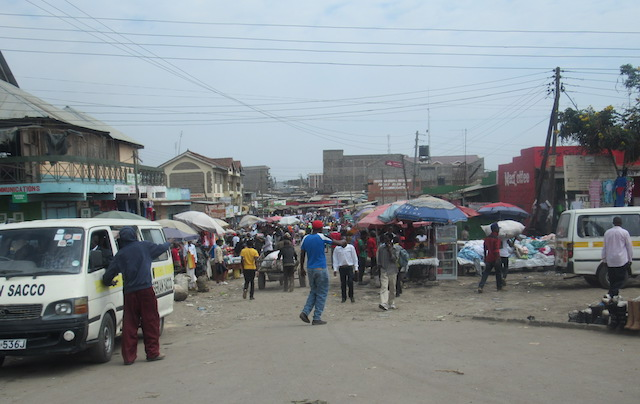 The crowded city streets of Nairobi are filled with people, cars, and vendors.