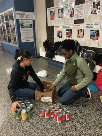 Freshmen Kynlee Johnson and Ashley Johnson help sort cans for the holiday food drive.