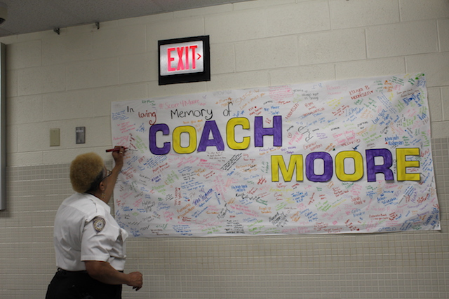 Security+guard+Jeanette+Walker+signs+a+poster+to+honor+Coach+Moore.+