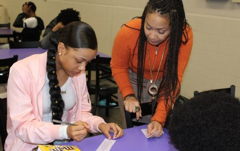 Sherron Hedgepeth-Sanders (Outreach Coordinator for the Newport News Commonwealth's Attorney) looks on as Taniyah Reaves signs the dating violence pledge.  Hedgepeth-Sanders talked with students during lunch to raise awareness of dating violence.