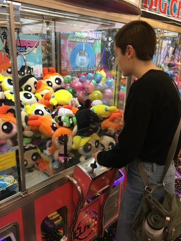 Junior Kelly Ritenour plays a claw machine game at the new TILT Studio.