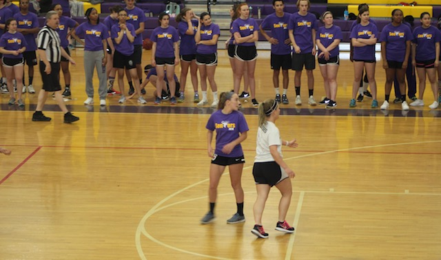 Action on the court is spectated by Menchville seniors along the side of the court.