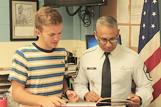 Chief Rambali looks at a yearbook with Senior Jeremiah Gaulding