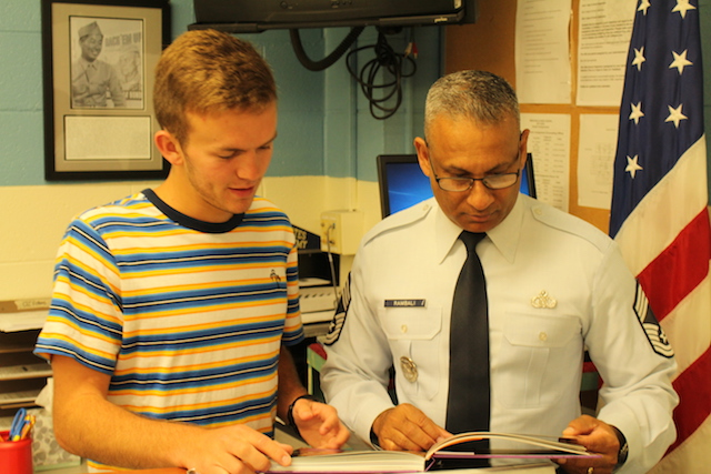 Mr. Rambali looks through the 2018 yearbook with a student.