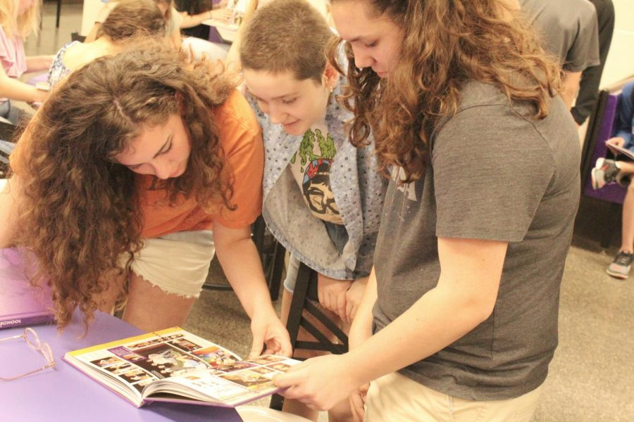 Students looking through a yearbook excitedly.