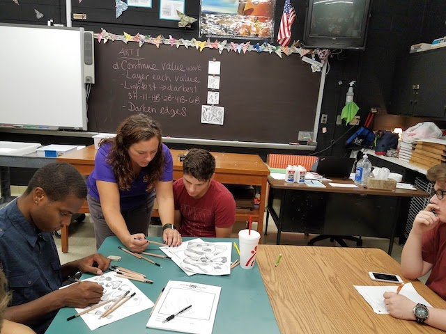 Mrs. Klapper helps students work on their art projects.