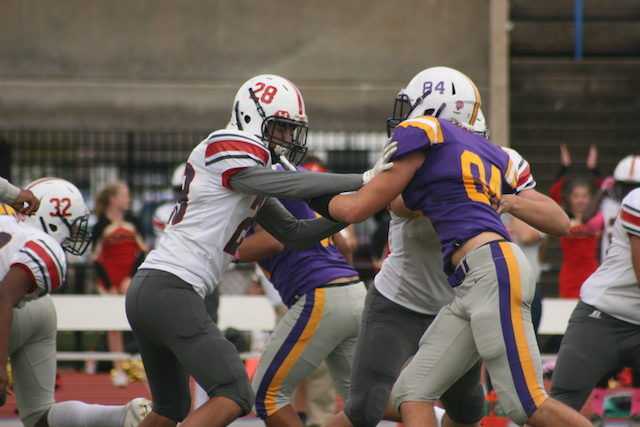 Varsity Football player holds back #28 at Menchville's Homecoming Football game.