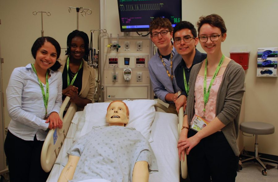 Students stand around the medical mannequin they just saved with CPR and electric shock from a coding situation.