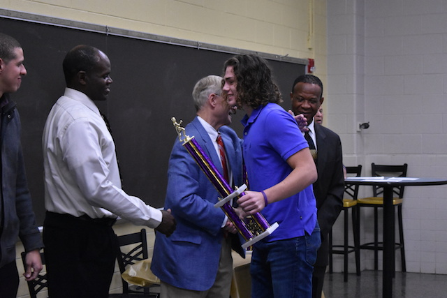 The football team Best Senior, James Norfleet, accepting his trophy at the Fall Sports Banquet.