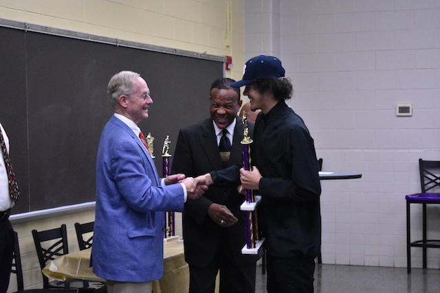 Anthony Hall shaking hands with Mr. Surry as he receives his award for Best Senior on the Boys Volleyball team.