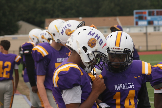 Two of Menchville's Varsity Football players on the sidelines at the annual homecoming game.