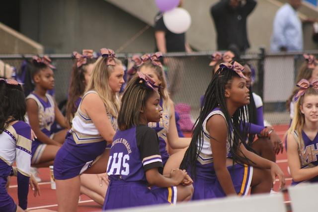 Cheerleaders kneeling at Menchville's annual homecoming game.