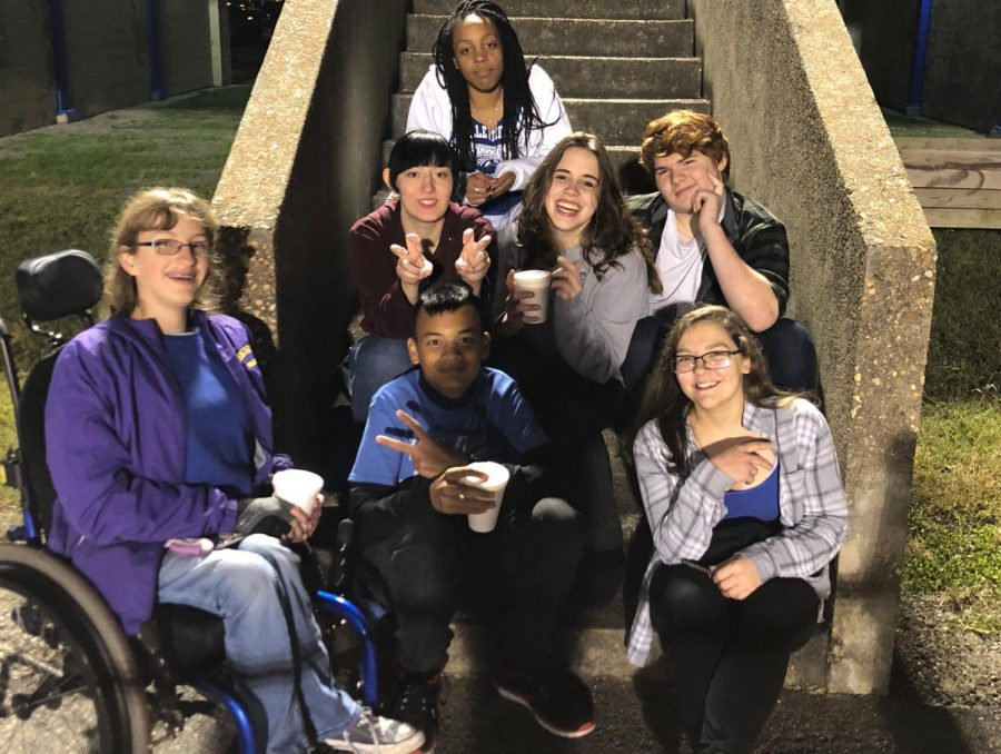 Lead2Feed members hang out by the stairs with their friend from Denbigh after half-time.