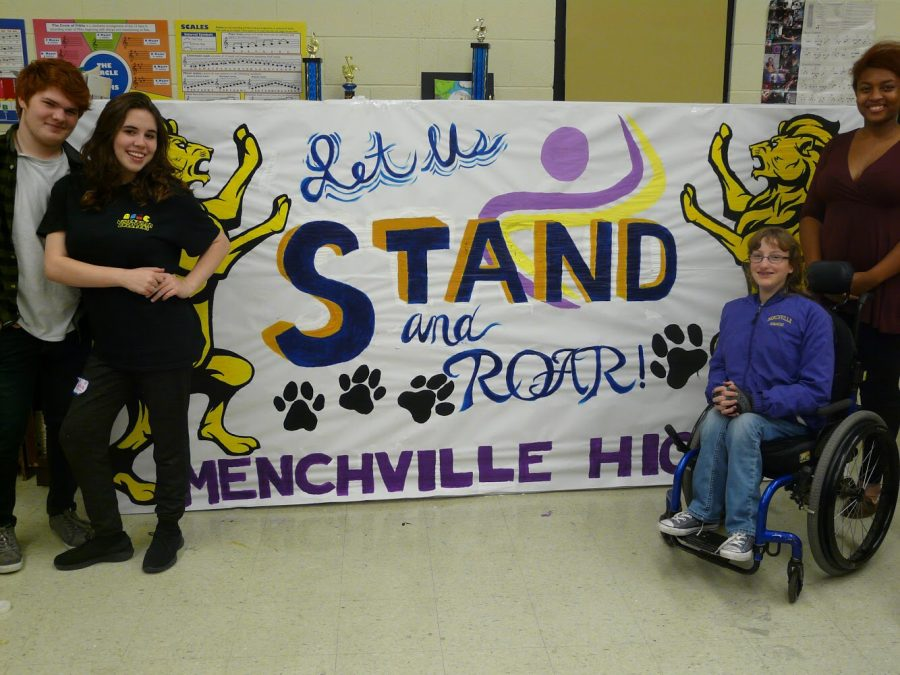 Lead2Feed members Sophia Ottofaro, Noah Reynolds, Beth Ellis, and Alexia Parker pose by their completed banner.