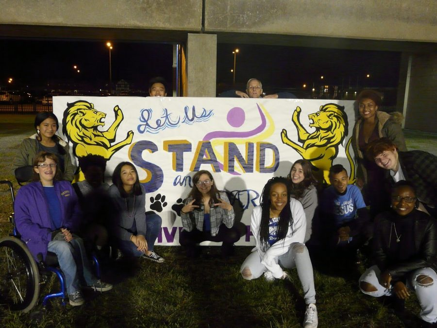 Menchville students and principal pose with their banner before half-time.