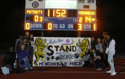 Menchville students and principal pose in front of the scoreboard before half-time.
