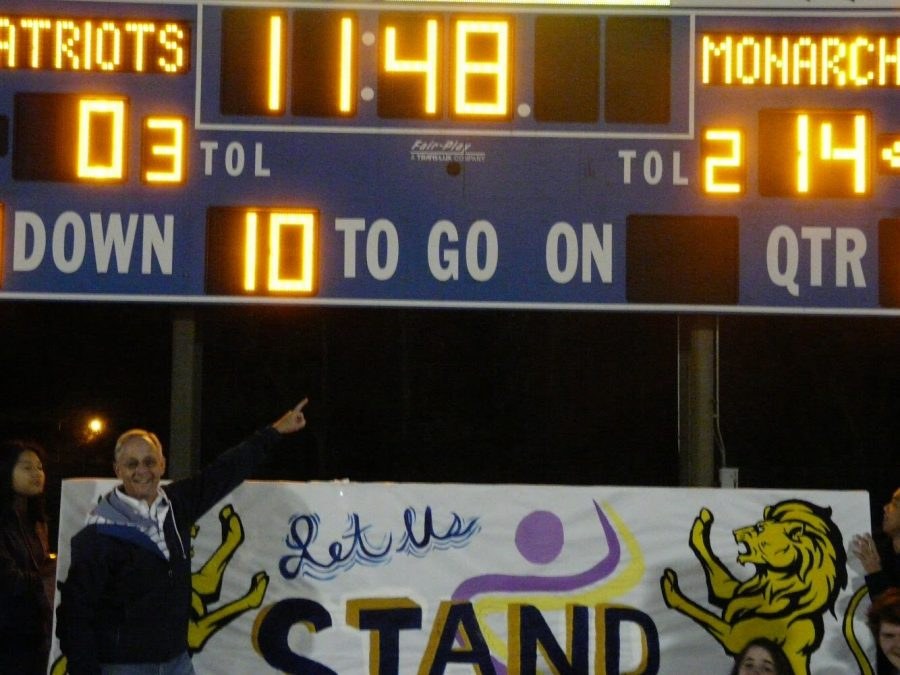 Principal Bobby Surry points to Menchville's score on the scoreboard before half-time.