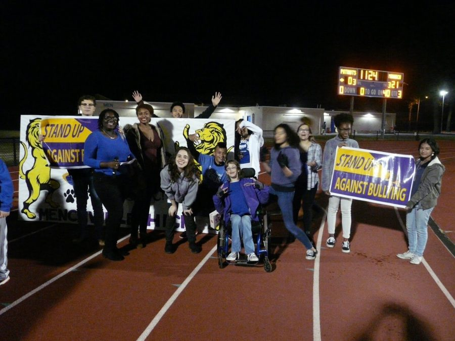 Menchville students pose for a picture  before they begin walking around the track at half-time.