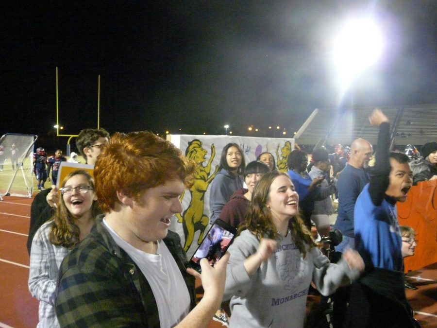 Menchville students march around the track with their banner.