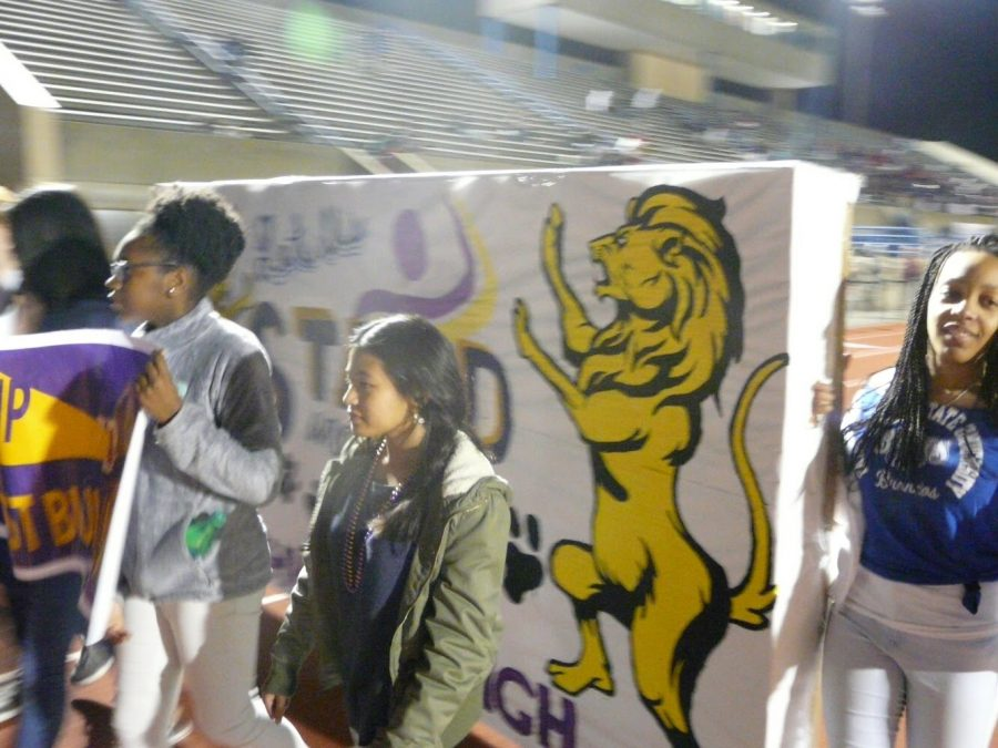 Lead2Feed members Sigrid Perkinson, Ashley Johnson, and Kailani Vera march around the track with their banner.