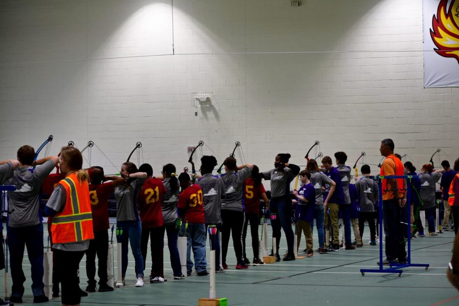 Archers lined up on the line, shooting a round of arrows.
