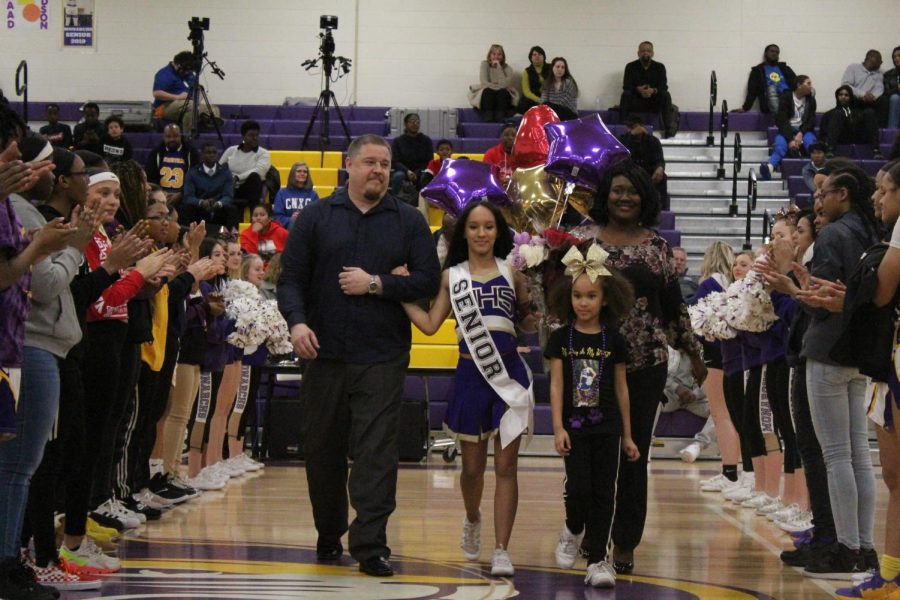 Senior Angel Brooks escorted by her mother, father, and sister.