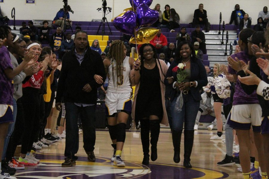 Senior Nyana Johnson walked by her mother, father, and sister.