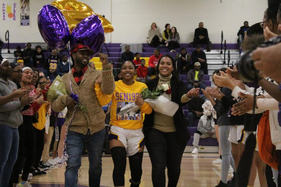 Senior Tyla Sawyer escorted by her mother and father.
