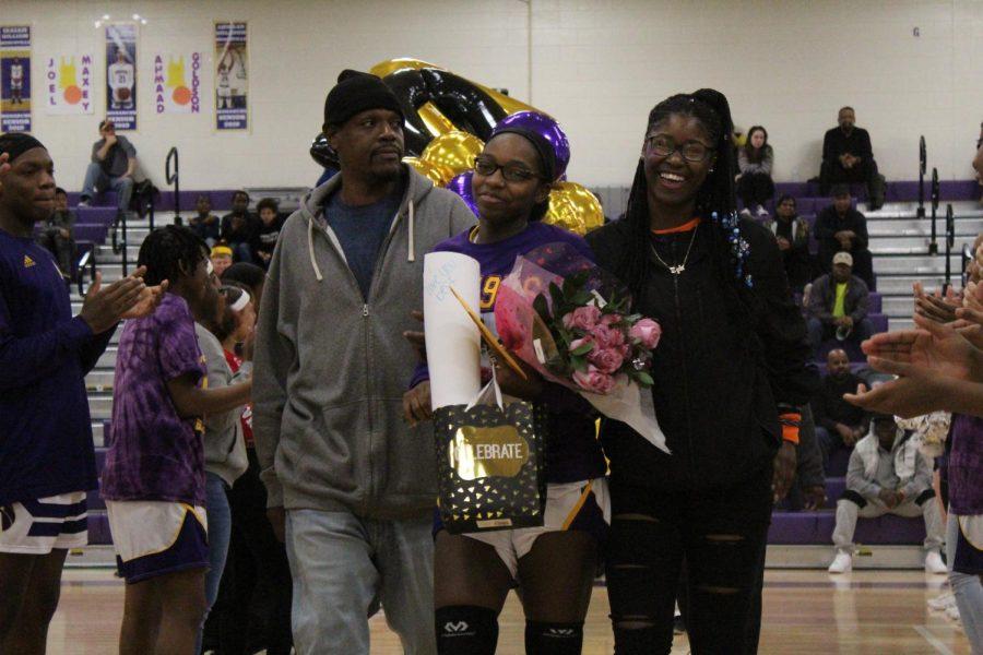 Senior Aja White escorted by her family