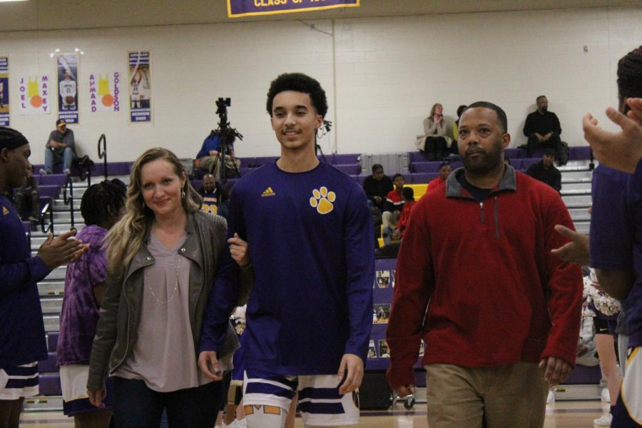 Senior Joel Maxey escorted by his mother and father.