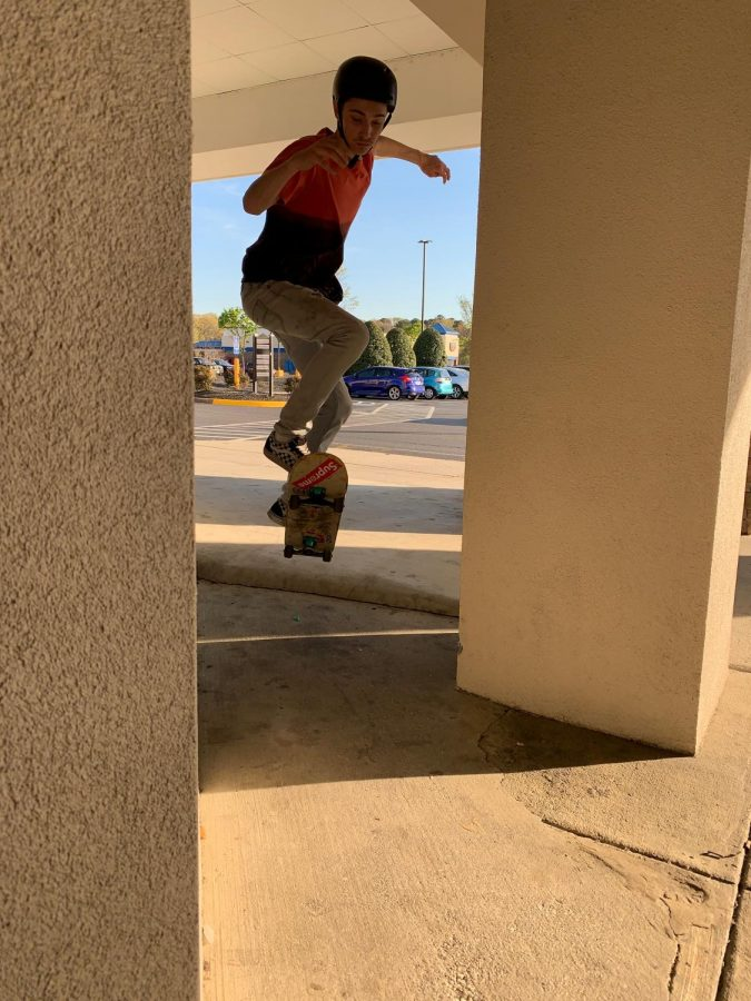 A skater does an ollie off of a ledge.