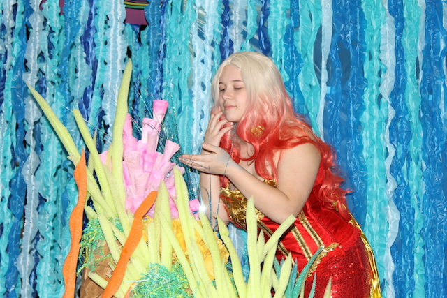 Sarah Clark sports her sequin-studded mermaid costume as she admires some coral.