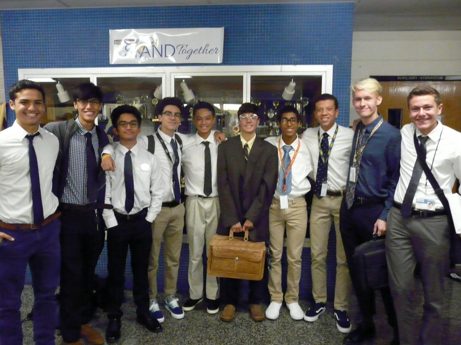 A+whole+staff+of+juniors+is+ready+for+the+rat+race%2C+complete+with+ties+and+leather+briefcases.
